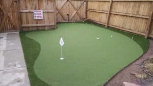 Artificial Turf Putting Green in Backyard with surrounding fence